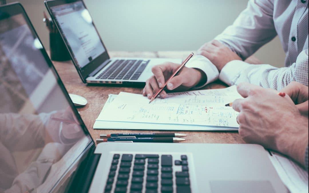 Vue de profil de deux ordinateurs portables avec un bloc-note au milieu et les mains de deux personnes travaillant ensemble comme lors d'une section de coaching commercial.