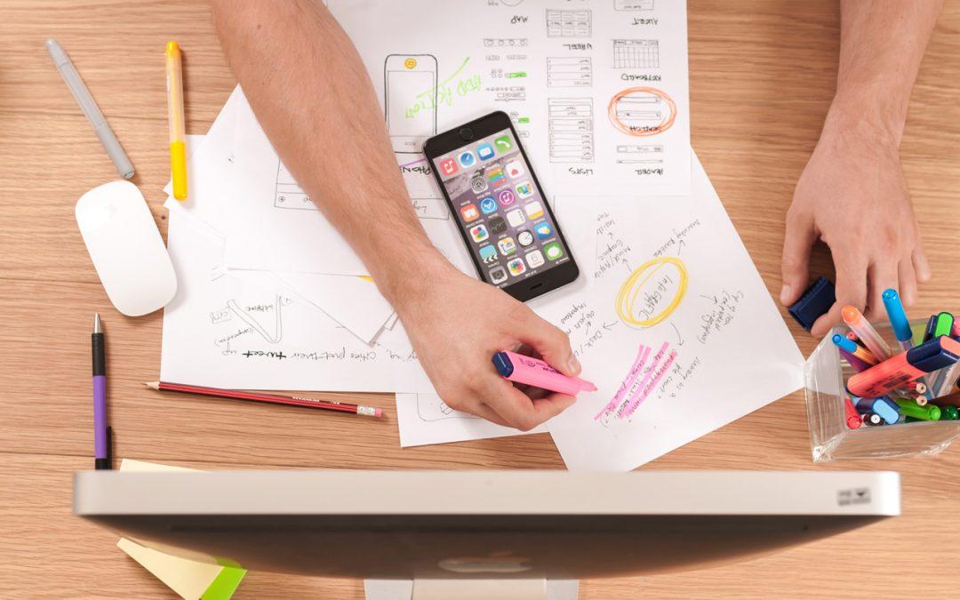 Vue aérienne d'une personne travaillant devant un ordinateur avec des documents, des crayons et un smartphone.