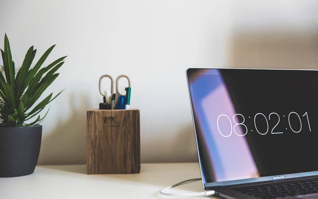 ordinateur portable posé sur un bureau et dont l'écran affiche une heure